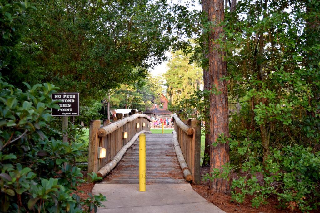 Atravesse a ponte, de onde já é possível ouvir a música e sentir o cheiro de madeira queimada.
