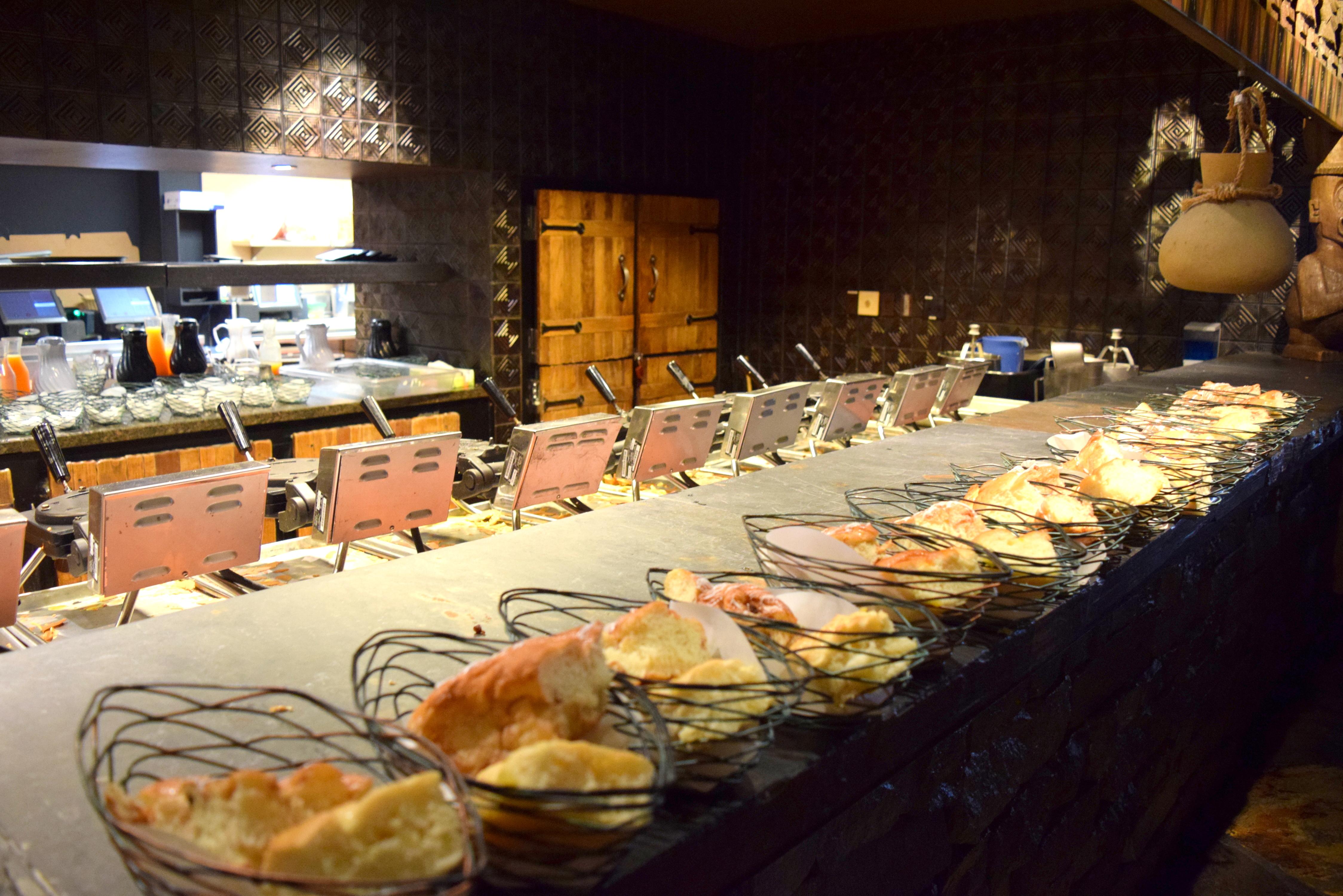 Travessa de pães à disposição no hall de entrada do restaurante. O Cast Member que irá encaminhar sua família para a mesa pega quantas travessas você desejar e leva à sua mesa.